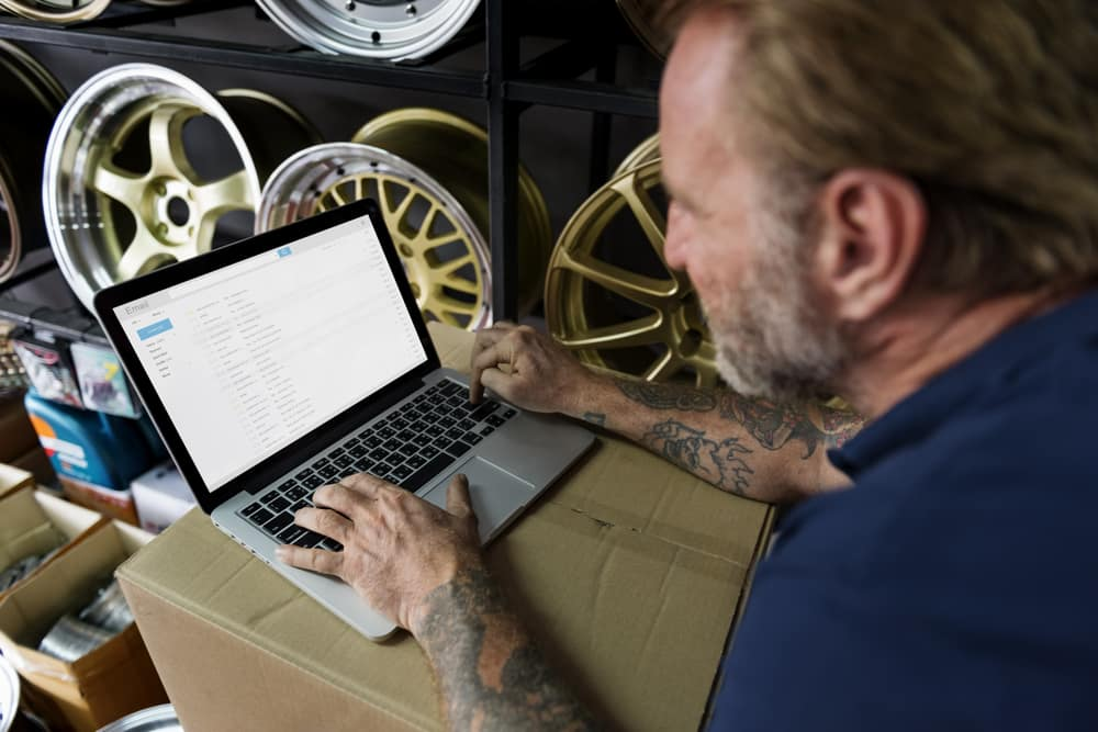 auto-mechanic-tattoos-checking-email-laptop.jpg